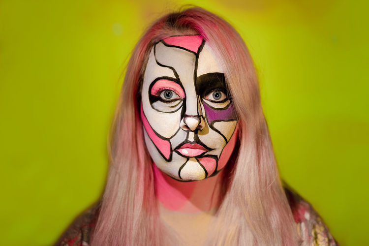 Close-up portrait of woman with face paint against green background