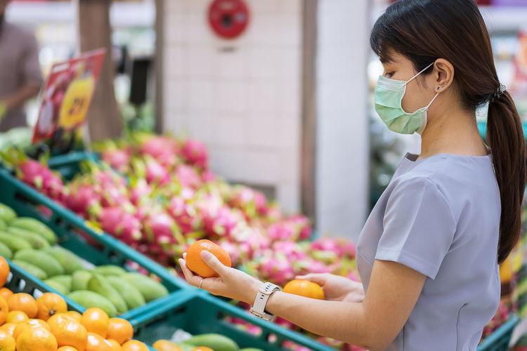 Side view of woman wearing flu mask standing in market