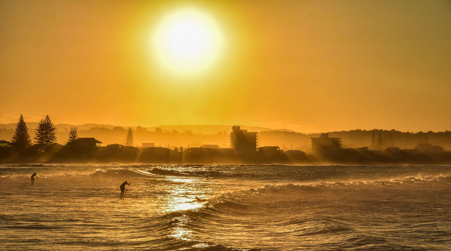 Surfing and sup at sunset on the baya of melbourne's magical austaliana, cold water, sea moved