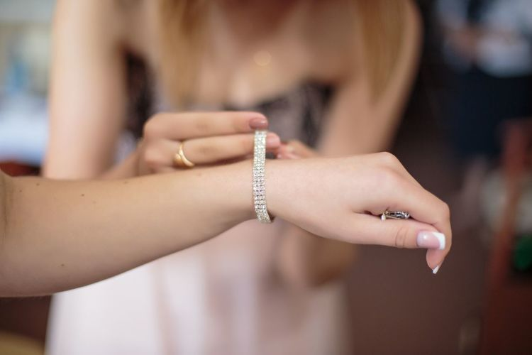 Midsection of beautician adjusting bride bracelet