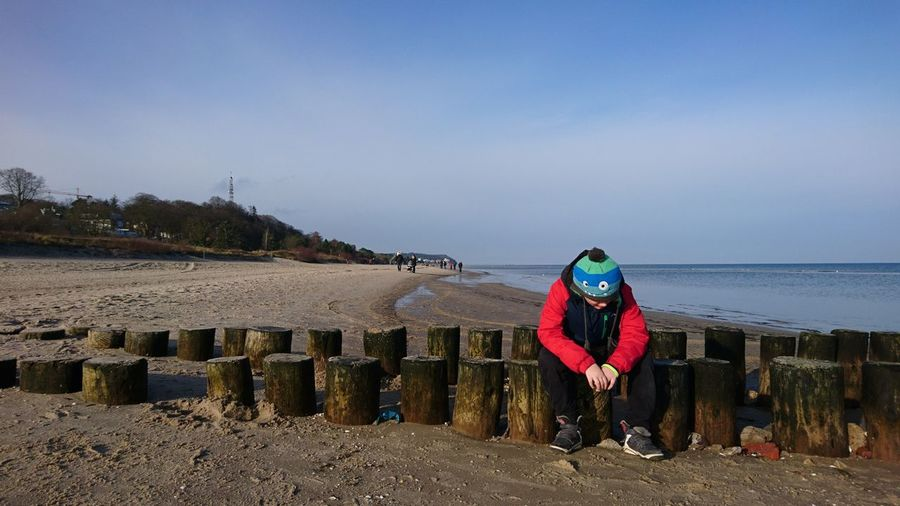 Full length of boy sitting on wooden posts at beach