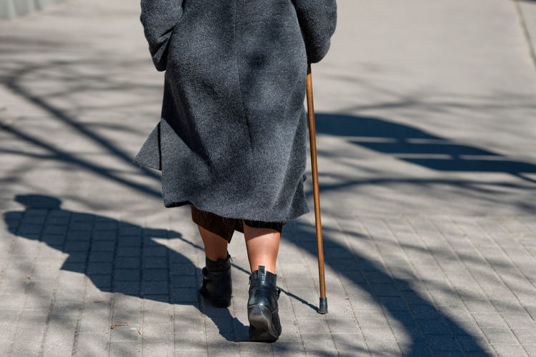 Low Section Of Woman With Cane Walking On Footpath