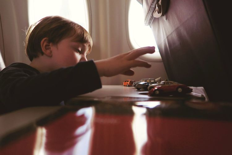 Boy playing with toy cars while traveling in airplane
