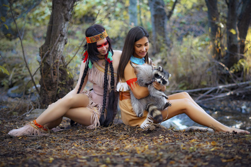 Young Women In Traditional Clothing Sitting With Raccoon In Forest