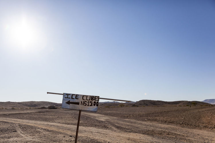 A welcome sign - ice cubes in the desert Arid Climate Clear Sky Communication Day Desert Humor Ice Landscape Nature No People Outdoors Road Sign Sand Sky Sunlight Text Western Script