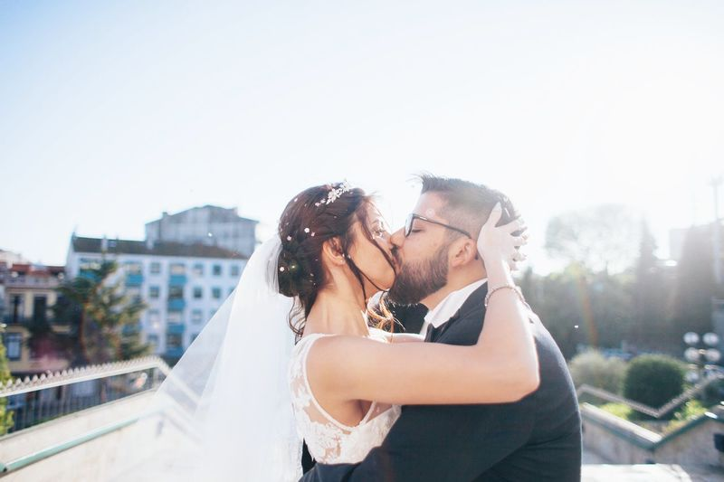 Close-up of couple kissing in city against sky
