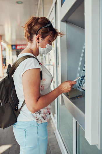 Woman withdrawing money from atm machine using debit or credit card standing outdoors in the street