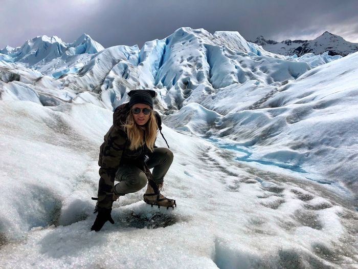 Portrait of woman crouching on glacier