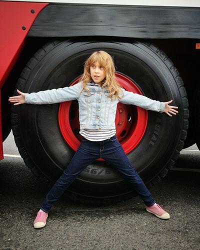 Full length of girl standing against tire