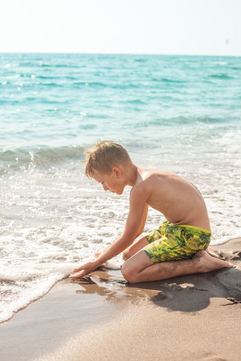 Shirtless boy playing on shore at beach during summer