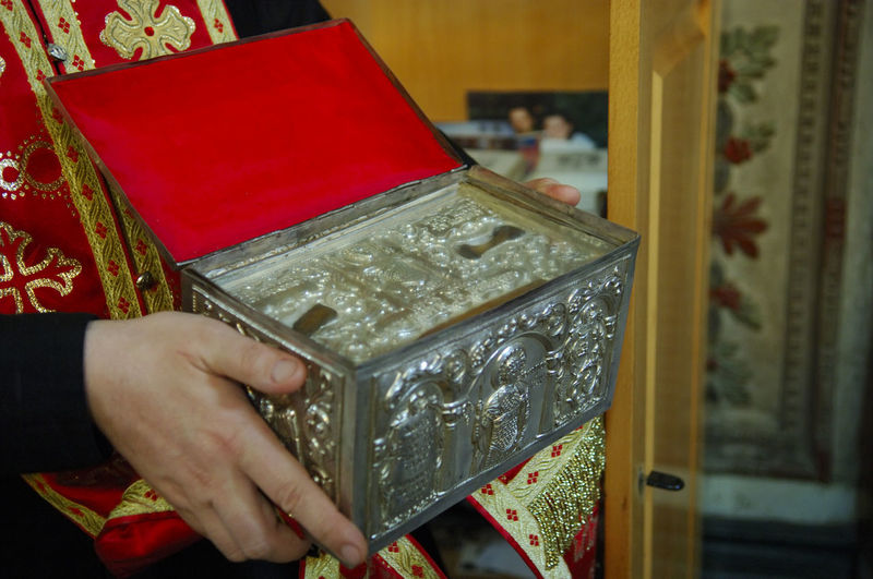 Cropped image of priest holding metal box