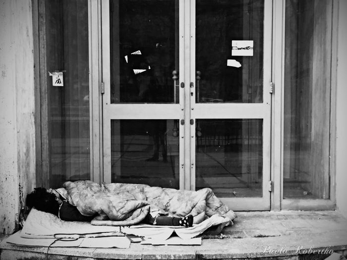 Homeless person sleeping on sidewalk