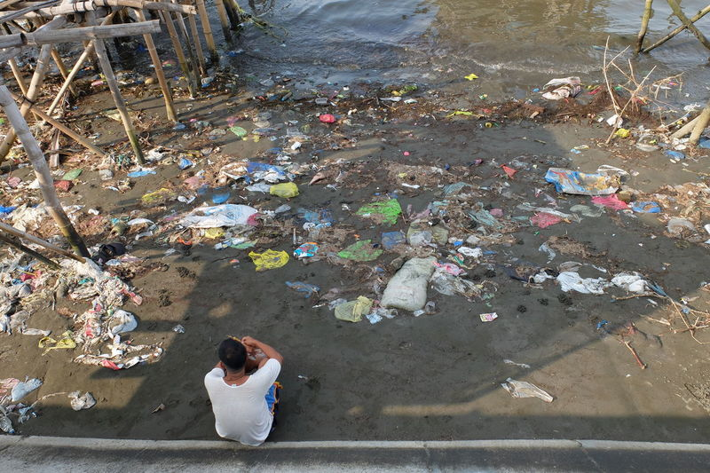 Rear view of man sitting by washed up garbage