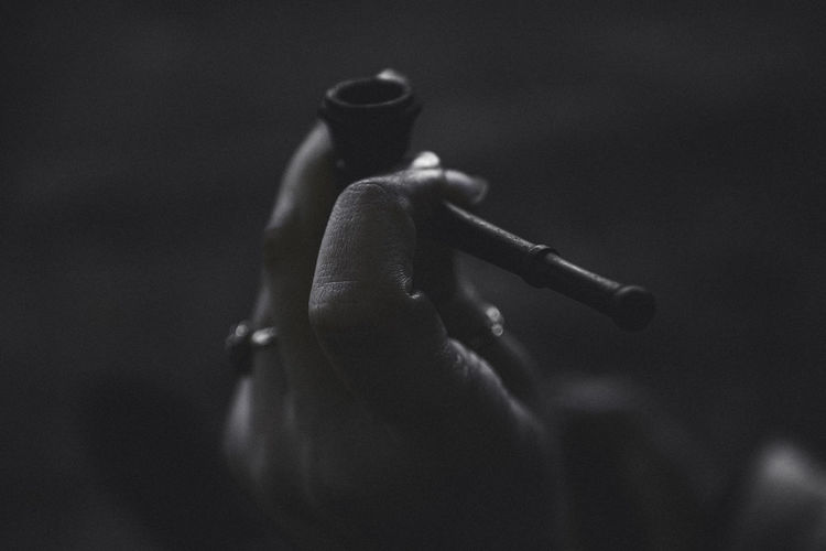 Close-Up Of Hand Holding Smoking Pipe