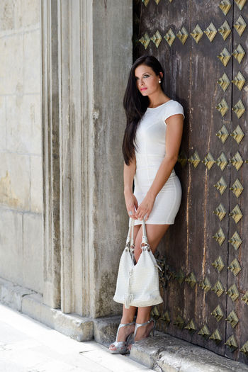 Portrait of a beautiful woman with bag in the street wearing white dress Dress Fashion Adult Adults Only Bag Beautiful People Beautiful Woman Beauty Casual Clothing Day Fashion Model Fashion Photography Full Length Lifestyles One Person One Woman Only One Young Woman Only Only Women Outdoors People Portrait Real People Standing Young Adult Young Women