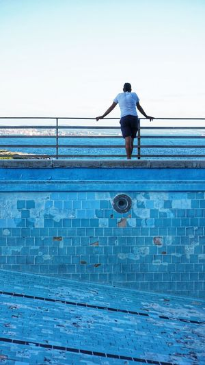 Rear view of man standing by abandoned  swimming pool against sky