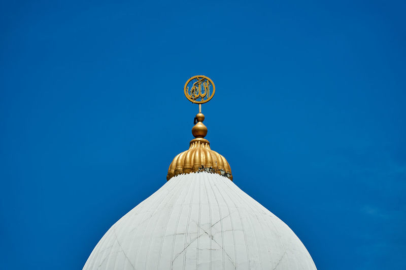 Low angle view of dome against building against clear blue sky