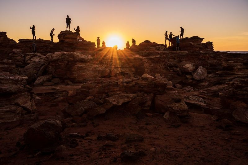 People on rock formation against sky during sunset