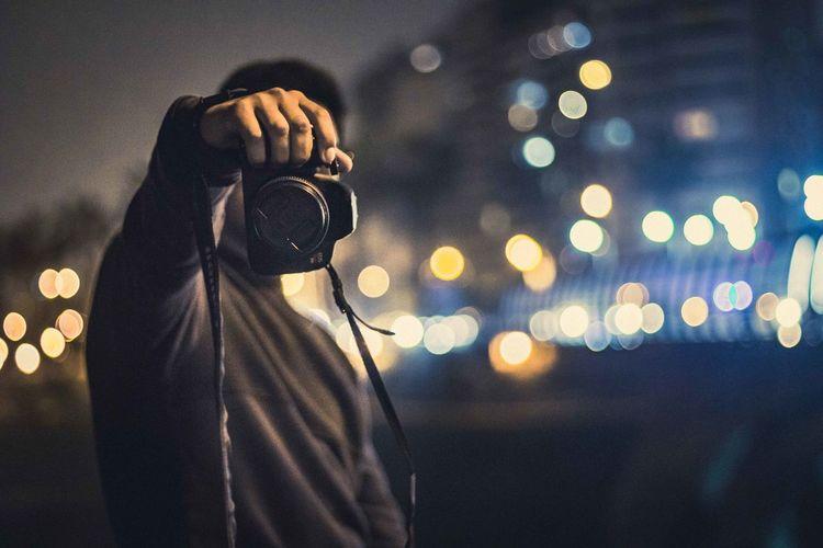 Man photographing illuminated camera against sky at night