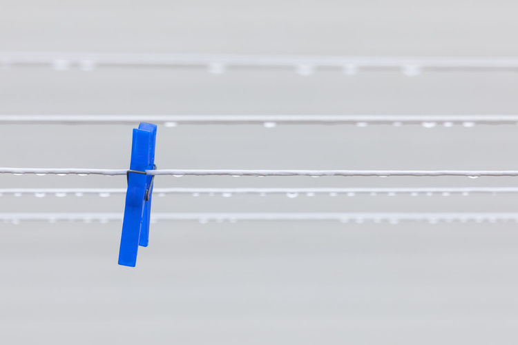 Raindrops on a white clothesline in front of a white house with one blue, plastic clothespin Copy Space Close-up No People Day White Background Minimalism Weather Rain RainDrop Striped Blue Pattern Plastic Metal In A Row Selective Focus White Color Simplicity Clothesline Hanging Focus On Foreground Equipment Laundry Clothespin Single Object