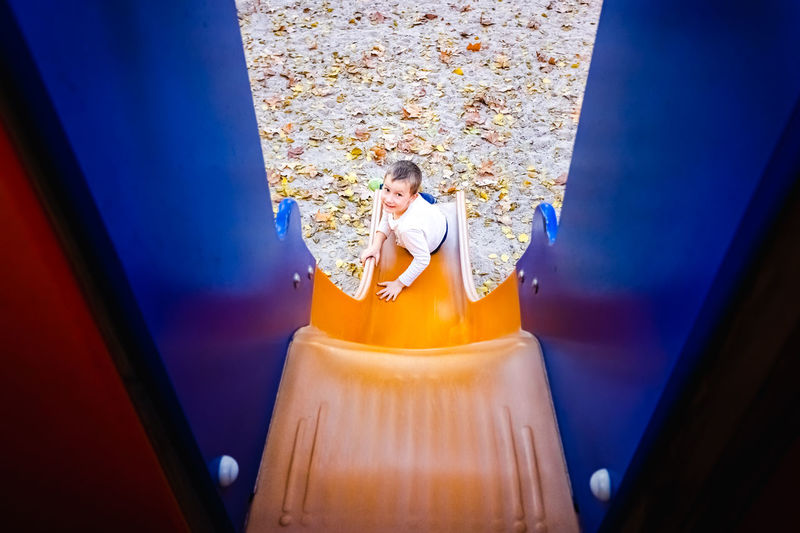 High angle portrait of boy sitting on slide in playground