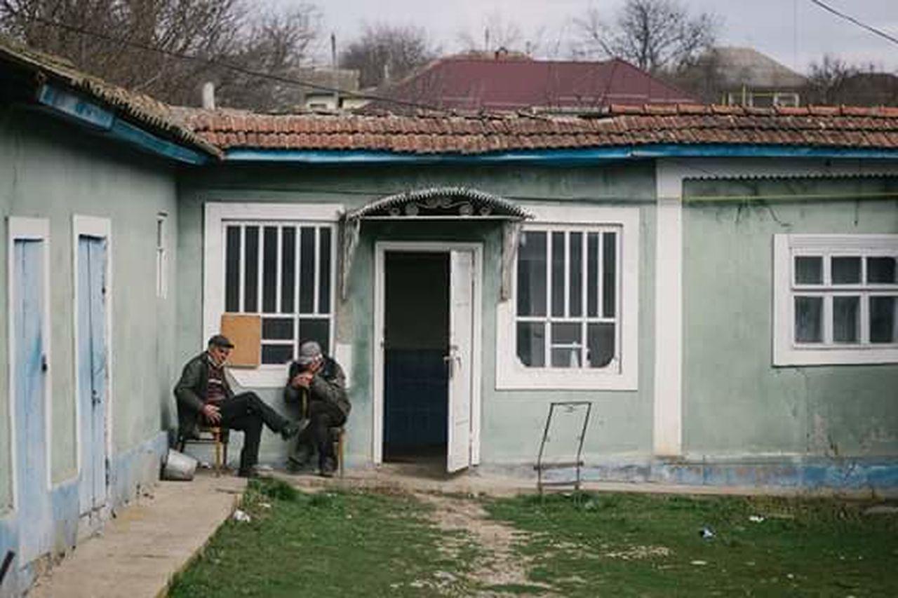 MEN SITTING ON STREET AMIDST BUILDINGS
