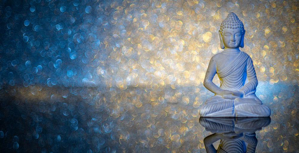 Digital composite of buddha statue against sky