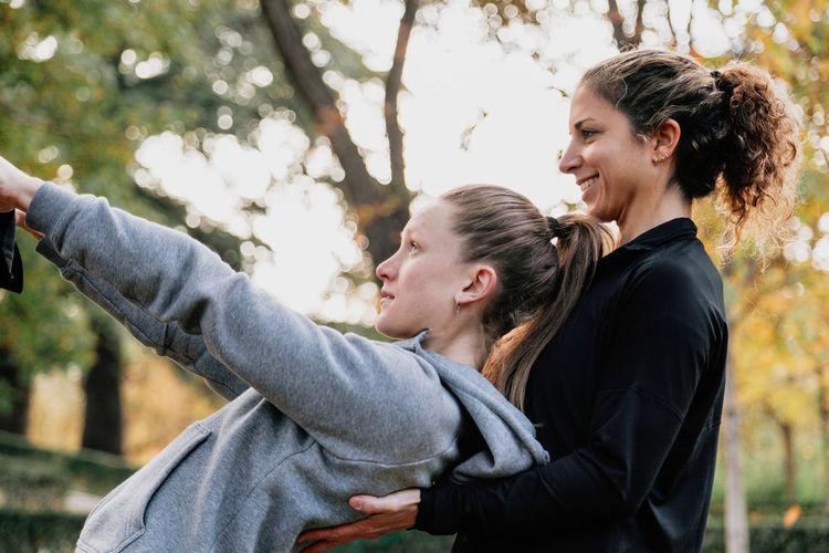 Smiling women exercising in park