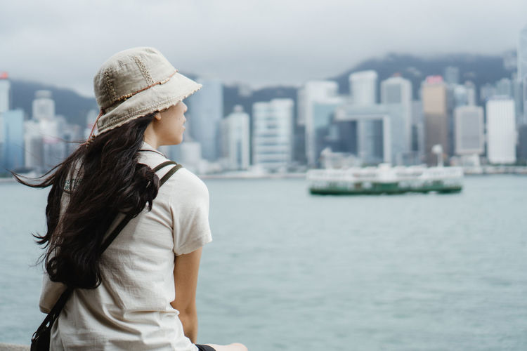 Rear view of woman standing against sea and cityscape