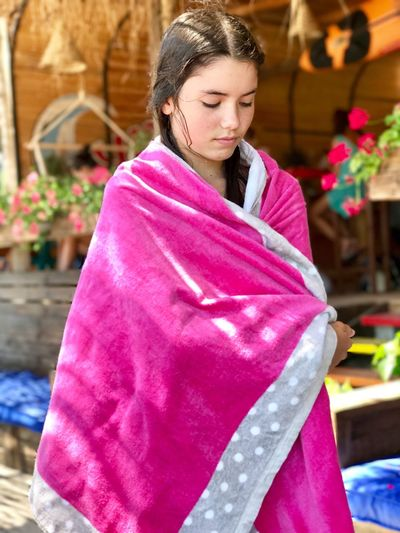 Girl wrapped in pink towel while standing outdoors