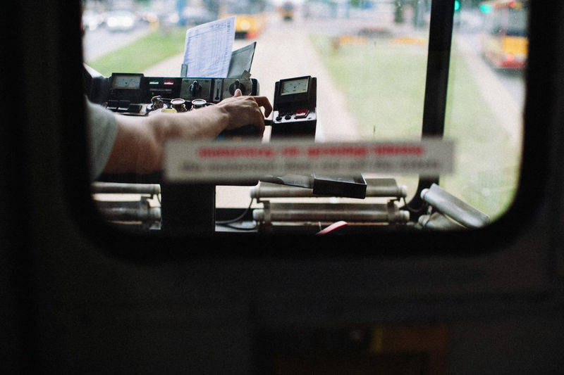 Cropped hand of driver driving bus seen through window