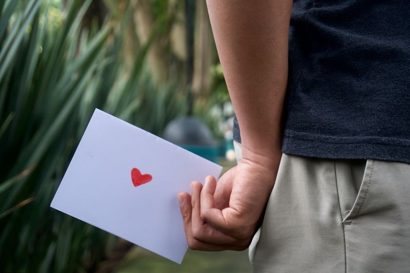 Midsection of man holding paper with red heart shape