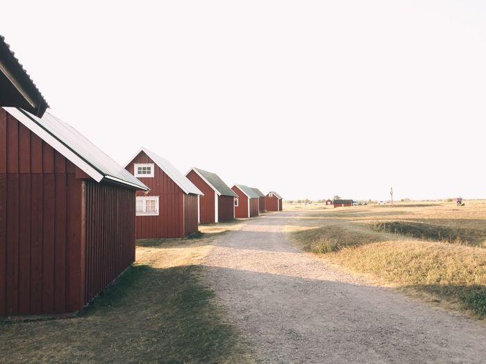 Houses amidst field against clear sky