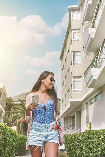 Full length of woman using mobile phone against buildings