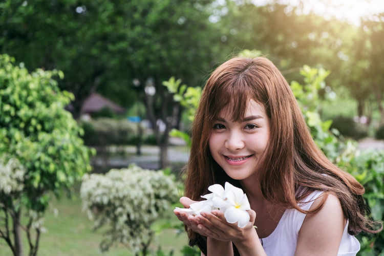 Portrait Of Smiling Young Woman Holding Flowers