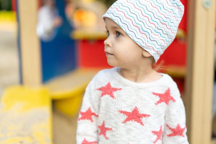 Cute girl wearing knit hat looking away
