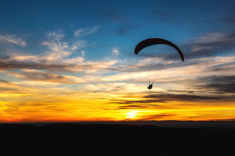 Adventure Beauty In Nature Day Extreme Sports Flying Leisure Activity Lifestyles Mid-air Nature One Person Outdoors Parachute Paragliding People Real People Scenics Silhouette Sky Sport Sunset