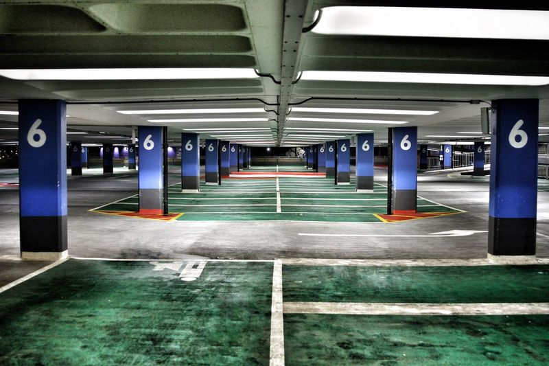 Level 6 of a deserted multi storey car park with colourful flooring and pillars. Parking Lot Parking Garage Multi Storey Car Park Multi Storey Multi Story Car Park Level 6 6 Six Architectural Column Illuminated Empty No People Built Structure Architecture Transportation Pillar Deserted Abandoned Parking Bay Number Numbers Inside