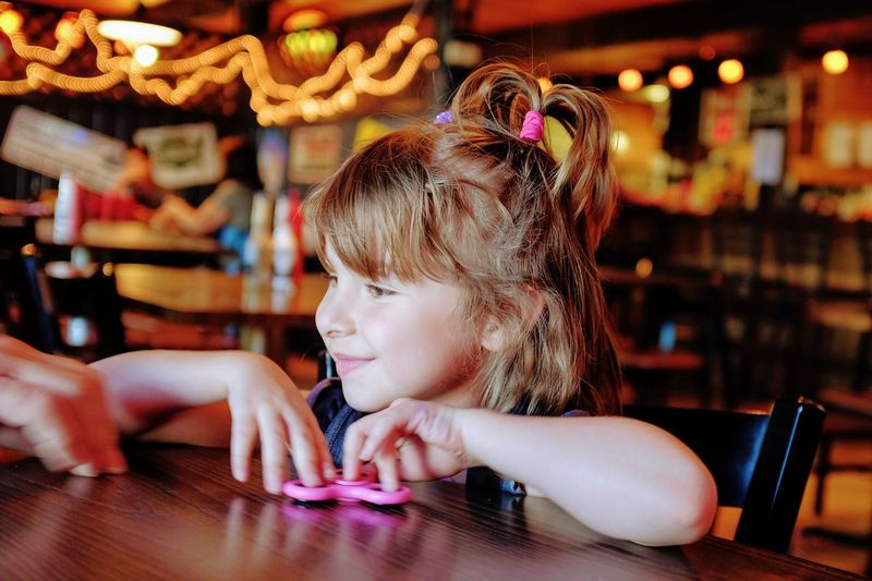 Close-up of smiling girl holding fidget spinner at table in restaurant
