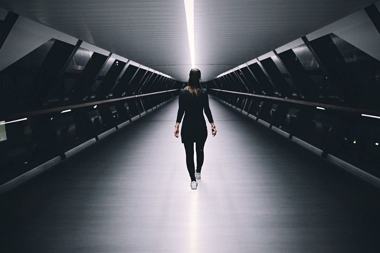 Rear View Of Woman Walking In Illuminated Footbridge