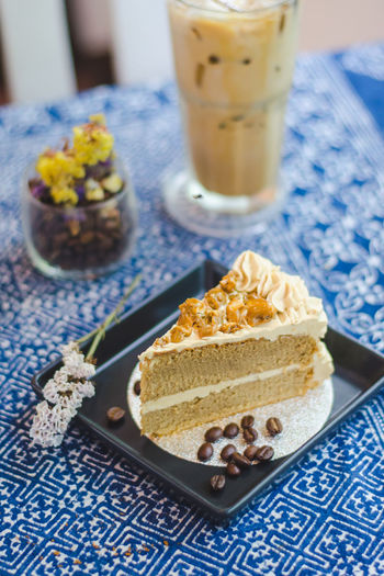 Cake In Plate By Coffee On Tablecloth At Cafe