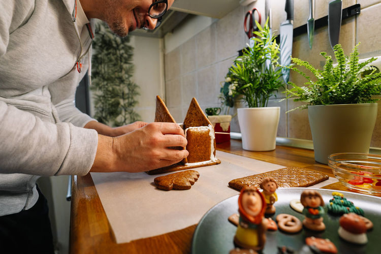 Midsection of man preparing gingerbread house on kitchen counter