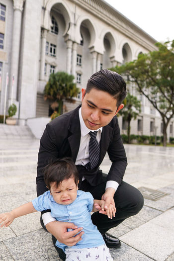Smiling man wearing suit holding son while crouching outdoors