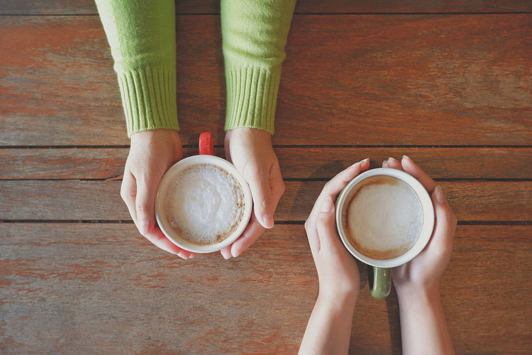 Two female playmate hands holding cups of cappuccino coffee on wooden tabletop in vintage tone style, top view with copy space, lifestyle in buddy concept Young Lifestyles Space Indoor Top View Hands Vintage Tone Cups Longsleeve Wood Wooden Tabletop Holding Playmate Buddy Female EyeEm Selects Human Hand Drink Frothy Drink Women Directly Above Hot Drink Coffee Beverage Froth Latte Cappuccino Caffeine Foam