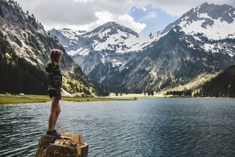 Full length of woman looking at lake against mountain range