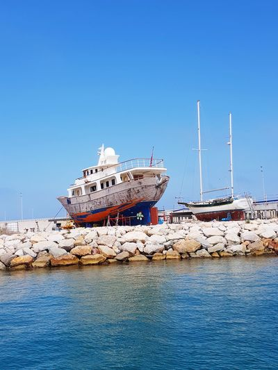 Ship moored on sea against clear blue sky