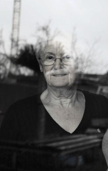 Portrait of senior woman looking through window