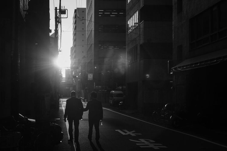 Architecture Building Building Exterior Built Structure City City Life City Street Lens Flare Men Mode Of Transportation Nature Outdoors People Real People Rear View Road Silhouette Street Sunlight Transportation Walking