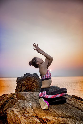 Woman Exercising On Rock Against Sea During Sunset