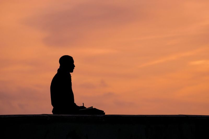 Silhouette Of Person Sitting Against Sky